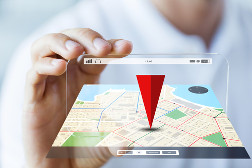 business, technology, navigation, location and people concept - close up of male hand holding and showing transparent smartphone with gps navigator map