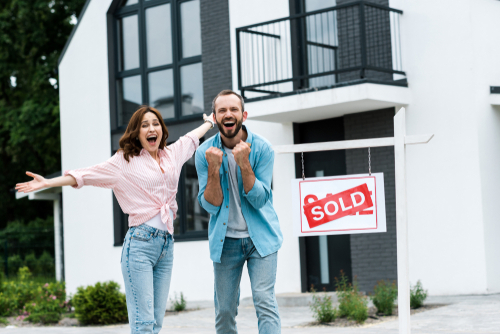cheerful man and woman celebrating about purchasing a new investment property in front of board with sold letters